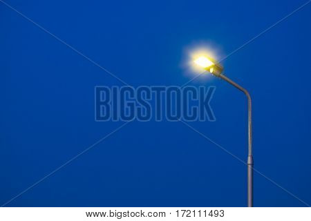 A part of top street light pole with dark blue sky background in twilight time.