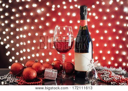 Christmas and New Year. Festive decorations, bottle of red wine and glass on the background lights.