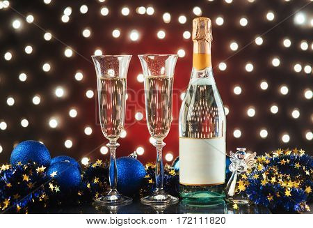 Christmas and New Year celebration with champagne. New Year holiday decorated table. Two Champagne Glasses against a dark background with gold shimmering light and bokeh