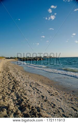 A sandy beach with tons of shells and crystal blue water - Vertical