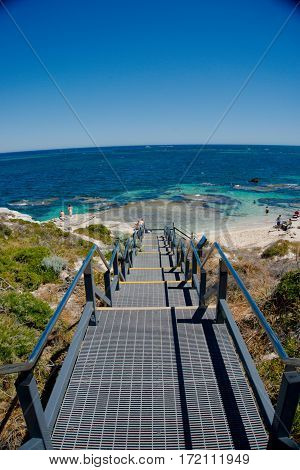 A stair on an island linked to the sandy white beach and crystal blue sea