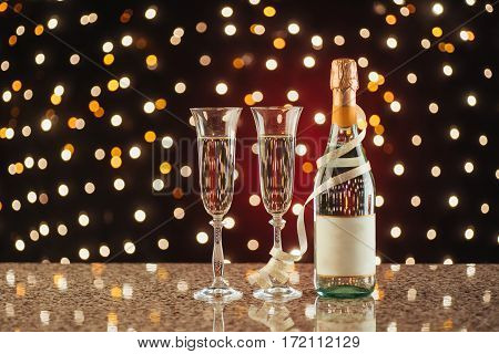 Christmas and New Year celebration with champagne. Pair of flute and bottle of Champagne for festive occasions against a dark background with gold shimmering light and bokeh