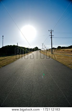 Large sun burning the dried grass at the side of the road in summer