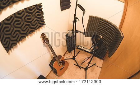 Guitar microphones and audio treatment panels in a recording studio room.