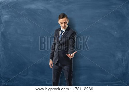 Businessman on blue chalkboard background holding one hand out and looking at it. Business and success. Business instruments. Problems and solutions.