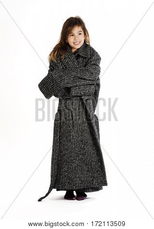 Funny little girl is wearing her mother's coat. Isolated with white background.
