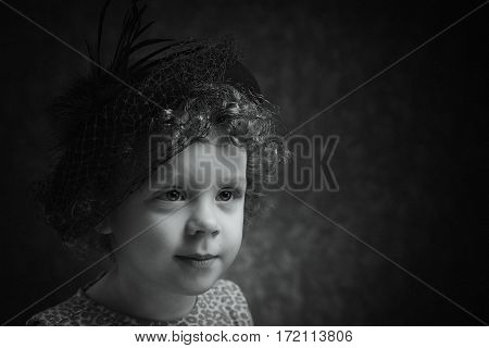 Black and white portrait of cute little girl with hat on her head. Positive expression of shy child.