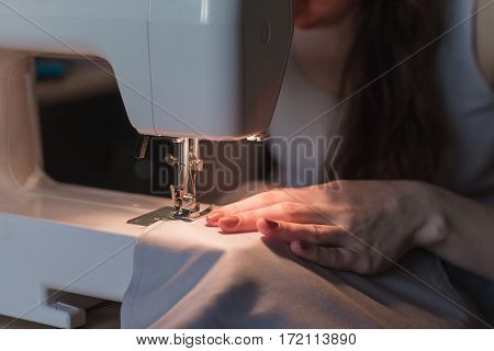 Women's hands behind her sewing. Sewing process.