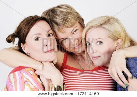 Portrait of three young women hugging each other. Isolated with light background.