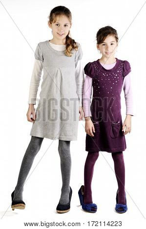 Two adorable sisters looking into the camera in their mother's high heels shoes. Isolated with white background.