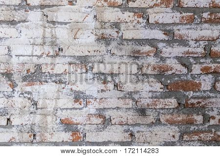 Old vintage brick wall with paint abrasive background texture.
