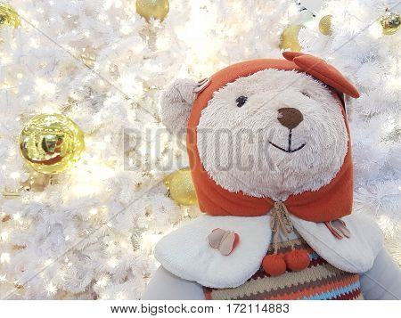 White bear doll with red hood on white coral Xmas tree with glitter golden mirror ball