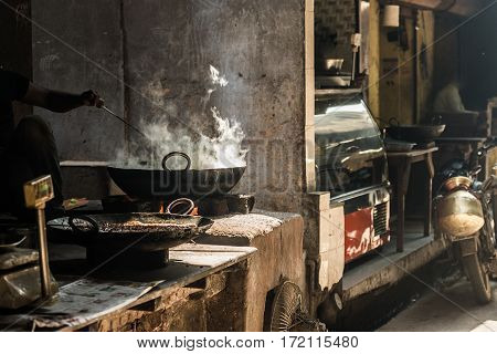 Unrecognizable Man Cooking In Fatiscent Big Pan Or Wok In A Small Street Food Stall. White Smoke Com