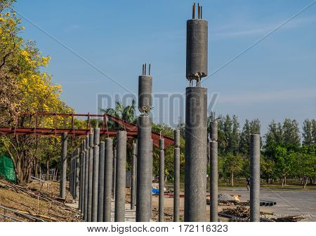 Construction method of connection on top of round concrete column with blue sky background.