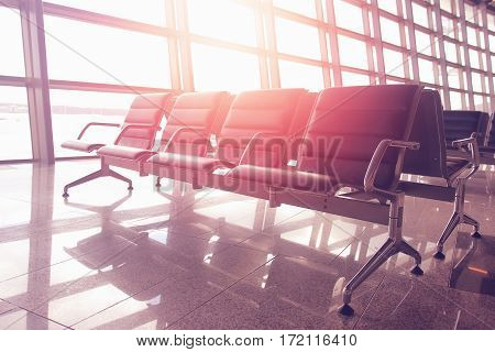 Seats for waiting flights at the airport at sunset. Colorful sun's rays fill the room with red hues. Concept of business and travel. Modern airport lounges.