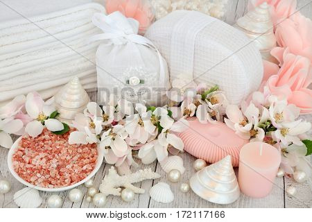 Skin care detox and ex foliating spa beauty treatment with himalayan sea salt, apple blossom flowers, pink rose soap petals, bathroom accessories and shells.