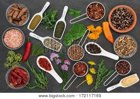 Large fresh and dried herb and spice selection on slate background, high in antioxidants and vitamins.