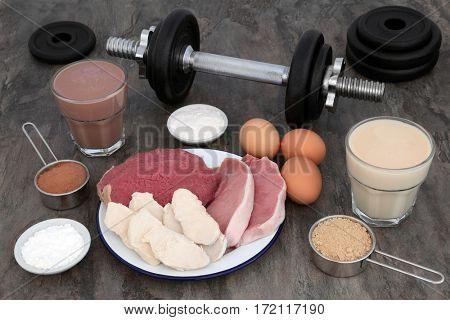 High protein food of meat and eggs with health drinks for body builders with weight training dumbbells and supplement powders.