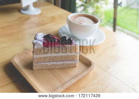 blueberry cake and hot coffee mocha with foam milk in countryside cafe