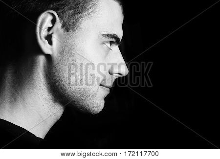 handsome guy unshaven smiling, dark portrait profile in low key black and white, low key portrait of young man