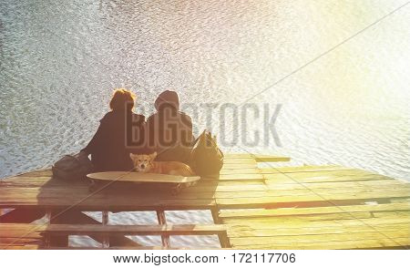 Handsome hiker  hipster lovers guy and the girl with a dog, longboard and sit on the lake pier at sunset, dreaming, talking, lifestyle