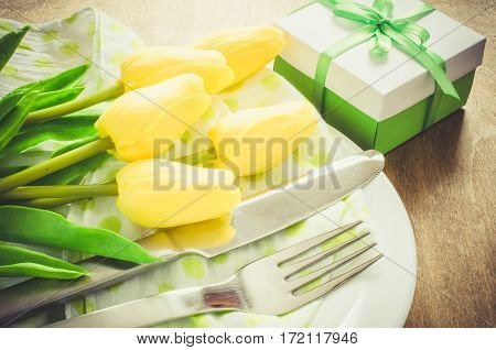Festive Table Setting in White Green and Yellow With Tulip. Concept Spring Easter or Mother's Day. Selective Focus. Toned Image.