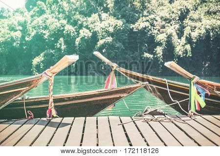 Longtail boats at Cheow Lan Lake on wooden jetty pier docks - Khao Sok national park in Thailand - Adventure travel concept with wanderlust feelings - Azure turquoise filter on sunflare halo sunshine