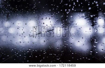 Rain drops on window with street bokeh lights