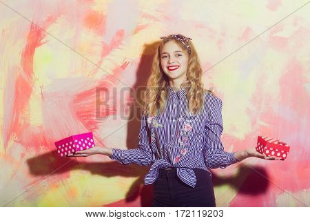 Cheerful pretty girl or beautiful woman with blond hair in blue striped shirt and stylish headband smiles with two red and pink polkadot gift boxes on colorful wall on abstract background