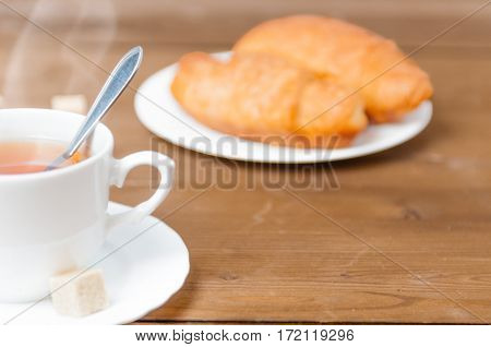 Fresh breakfast with cup of tea with steam above it and a croissant. Festive breakfast Valentine's Day with love. Tasty and healthy breakfast. Shallow depth of field. Close up.