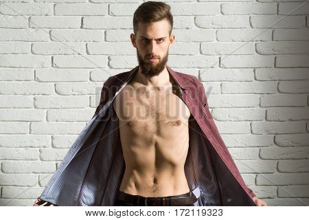 handsome bearded man or hipster guy with serious face and bare slim torso in fashionable purple shirt on white brick wall background
