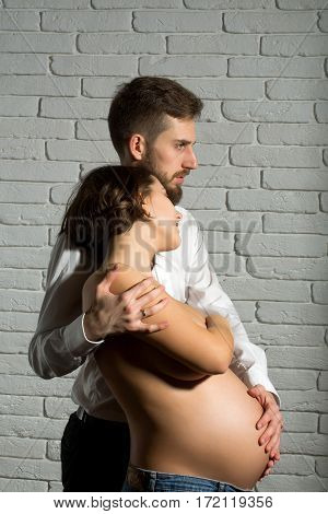 family parent couple of pretty smiling sexy woman or cute pregnant girl with naked round belly or abdomen and handsome bearded man hipster in white shirt on brick wall background at mothers day