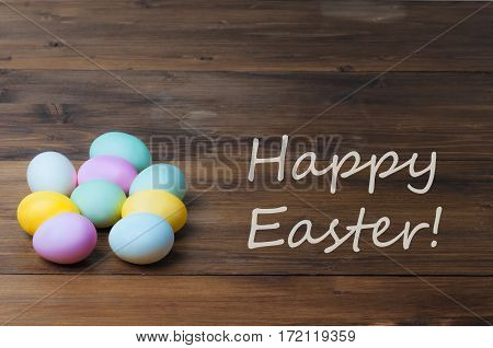 Colorful Easter eggs on vintage wooden table, rustic background, holiday concept with text - Happy easter. Copyspace, textspace.