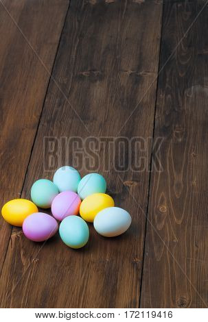 Colorful Easter eggs on vintage wooden table, rustic background, holiday concept. Textspace, copyspace.