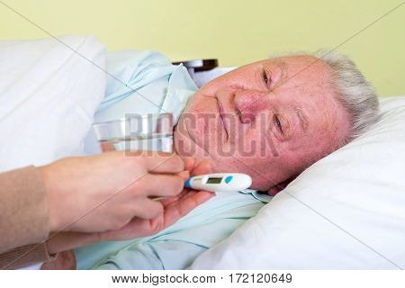Picture of a bedridden elderly man having high temperature