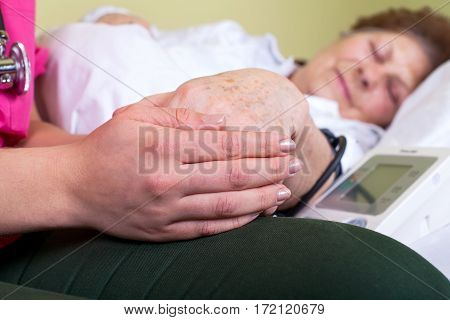 Close up picture of a bedridden woman being helped by her carer