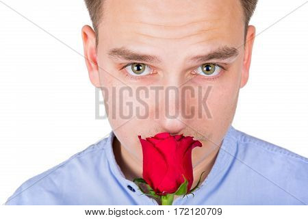 Close up picture of a handsome young guy smelling a red rose