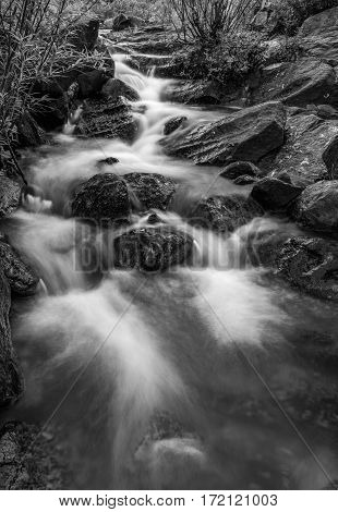 A black and white river scene with large boulders and lush vegetation in Vietnam.