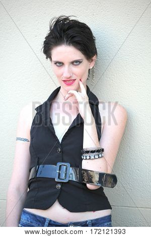 Female beauty fashion model against a wall outside.