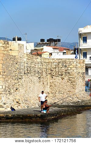 IERAPETRA, CRETE - SEPTEMBER 18, 2016 - Fishermen in front of Kales Venetian fortress at the entrance to the harbour Ierapetra Crete Greece Europe, September 18, 2016.
