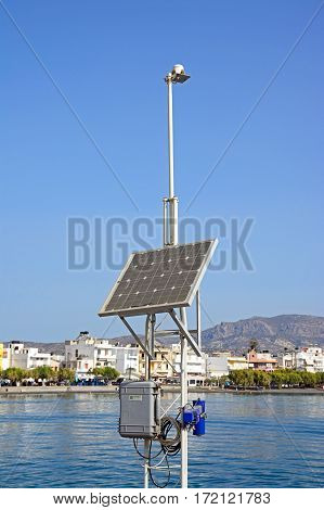 IERAPETRA, CRETE - SEPTEMBER 18, 2016 - Solar panel used for harbour navigation lights in the harbour with views towards the town Ierapetra Crete Greece Europe, September 18, 2016.