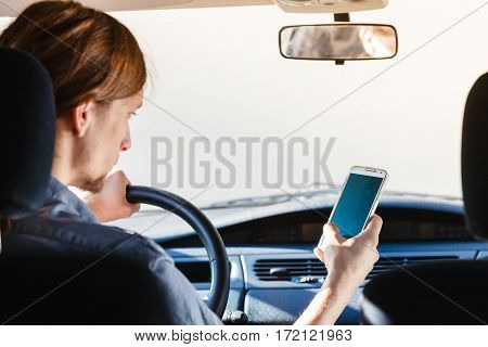 Modern technology concept. Man using mobile phone while driving car checking social media or setting navigation.