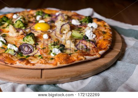 Delicious fresh homemade pizza with onions, vegetables and cheese on a wooden table. Copy space. close-up.