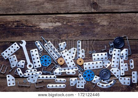 various metal details and a wrench on a wooden surface.background.top view.