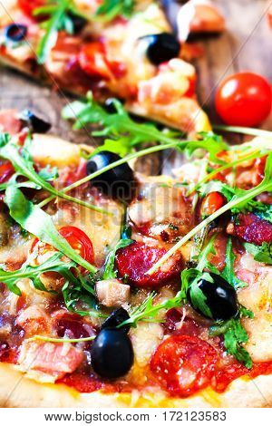 Hot pizza slice with Pepperoni melting cheese on a rustic wooden table close up.