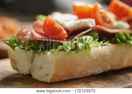 open sandwich with prosciutto, mozzarella and tomatoes on kitchen table, shallow focus