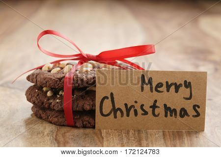 stack of homemade chocolate cookies with hazelnuts tied with ribbon on wood table and paper card, shallow focus