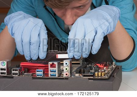 Young Man With Gloves  Installing Ram Ddr4 Memory Module In Slot On Motherboard