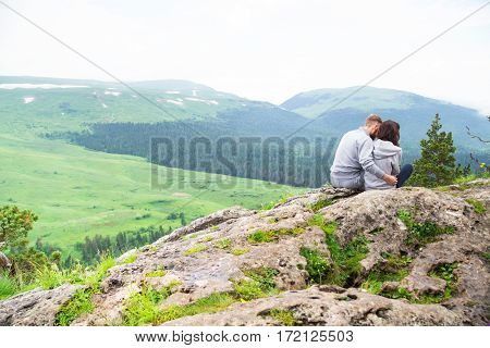 Loving Young Hipster Couple Sitting On A Mountain, Hugging And Looking Away, Love And Feelings Conce