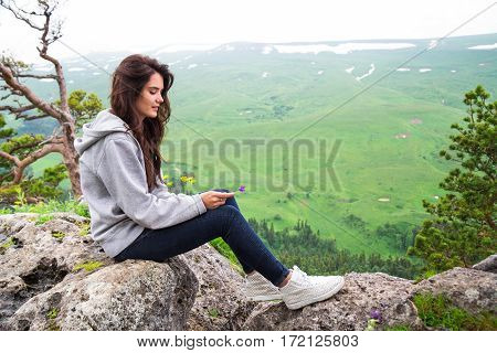 Pretty Young Woman Sitting On Mountain Top And Contemplating Landscape